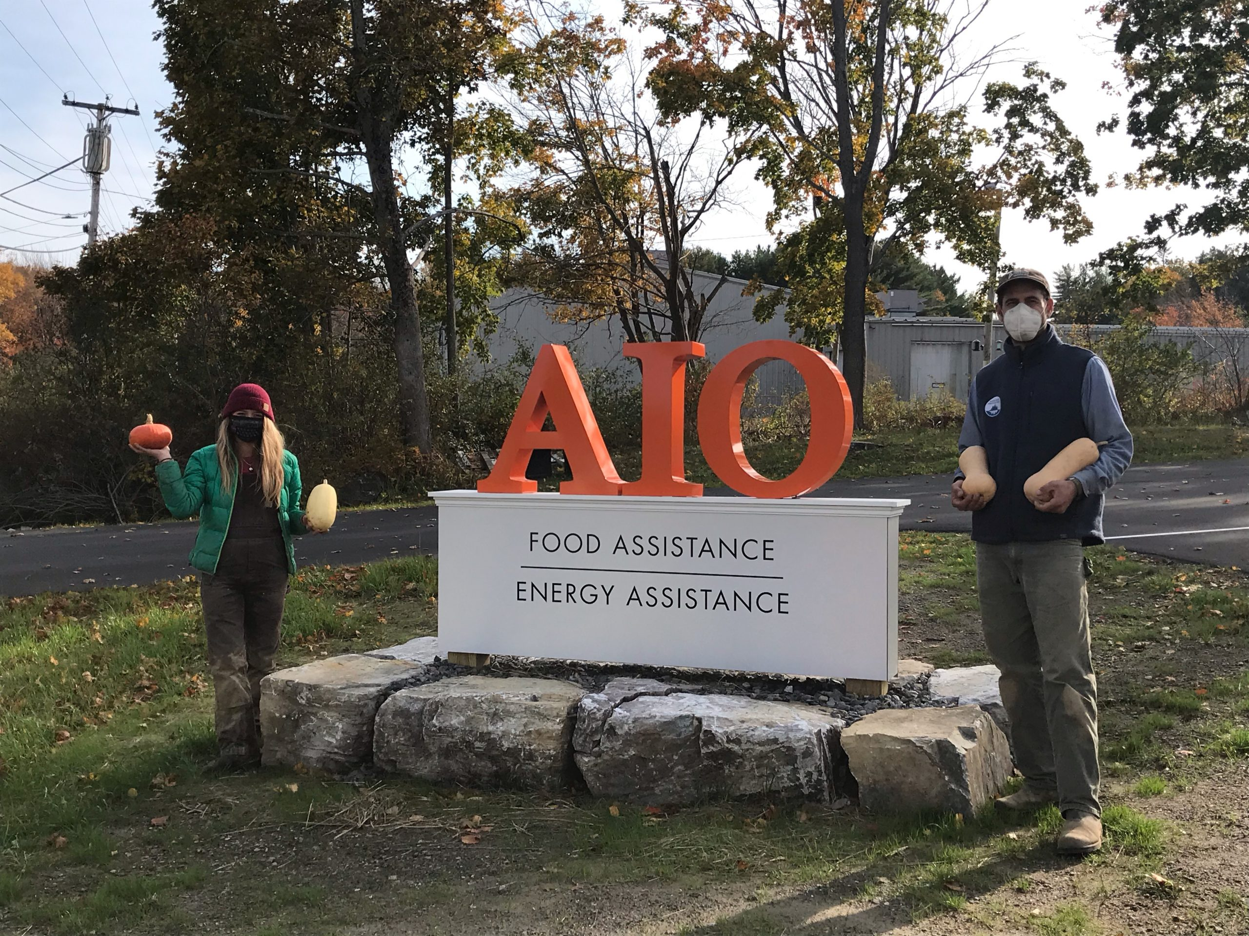 Left to right: MOFGA apprentice, Liv Caron, and MCHT's Erickson Fields Farm Manager, Aaron Englander, stand by the sign at AIO's new building in Rockland.
